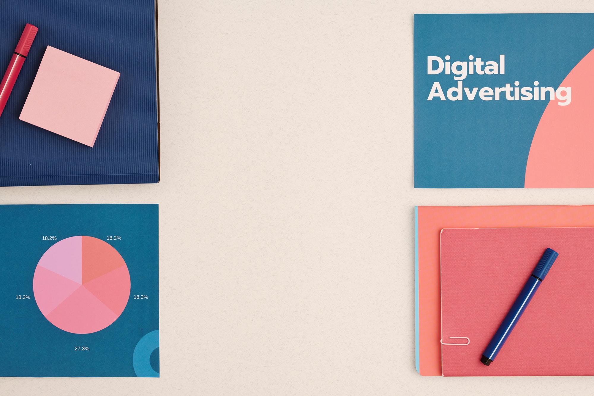 Flatlay of digital advertising brochures surrounded by other working supplies